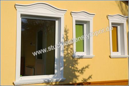 Fertig eingebaute Fensterverzierung mit Fenstergiebeln, L-förmigen Laibungsverkleidungsprofilen und Fensterbänken