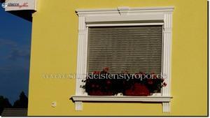 Fensterumrandung an einer gelben Hausfassade